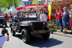 May 2018, Canadian war veteran military jeep parade Liberation Day, Netherlands. Elderly Canadian war veteran is driving in military jeep old timer and making stock photography