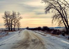 Canadian Winter Sunset. Lone road on Canadian farmland skirting the Rocky mountains at sunset Royalty Free Stock Images