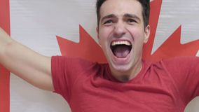 Canadian Young Man Celebrates holding the Flag of Canada in Slow Motion. High quality stock photography