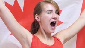 Canadian Young Woman Celebrates holding the Flag of Canada in Slow Motion. High quality stock photos