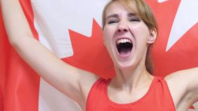 Canadian Young Woman Celebrating while holding the Flag of Canada in Slow Motion stock image