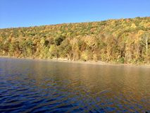 Canadice Lake, one of New York`s Finger Lakes. Bare trees on the shore of the clear, still water of Canadice Lake, one of Finger Lakes in New York, in horizontal stock image