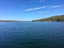 Canadice Lake, one of New York`s Finger Lakes. The clear, still water of Canadice Lake, one of Finger Lakes in New York, in horizontal orientation in Autumn royalty free stock photos