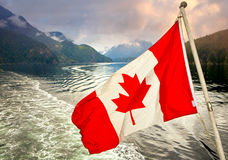 Canadian flag in front of inlet. Indian Arm, Vancouver Royalty Free Stock Photos