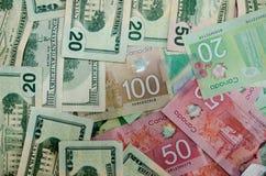 Canadiense y dólares de la moneda de los E.E.U.U. de la denominación 20,50 y 100 imagen de archivo libre de regalías