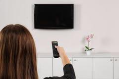 Canais de comutação da mulher no aparelho de televisão imagens de stock