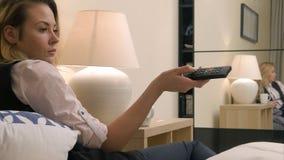 Canais de televisão fêmeas do interruptor da mão na cama Imagem de Stock Royalty Free