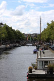 Canal in Amsterdam with houseboats lining the waterfront. Houseboats parked along the waterfront by the river Amstel in Amsterdam, The Netherlands. Sunny day Stock Photo