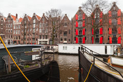 Canal of Amsterdam, Netherlands. Colorful traditional living houses and houseboats along the canal in Amsterdam, Netherlands. Warm vintage tonal correction Stock Photo