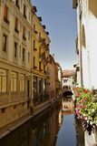Canal, Annecy, France. Canal flowing between three story historic buildings in Annecy, Northern France. Beautiful reflections on water, flower pots on window Stock Photo