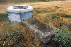 Canal antiguo abandonado para el ganado cerca del cerrado bien de piedra Foto de archivo