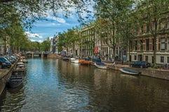 Canal arbolado con los edificios de ladrillo viejos, los barcos y el cielo azul soleado en Amsterdam Imagen de archivo libre de regalías