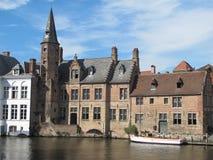 Canal, barco y edificios viejos en Brugges Fotos de archivo