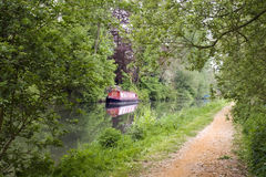 Canal with barge. Red barge on a tranguil part of the Kennet-Avon canal, England Royalty Free Stock Image