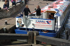 Canal barge in lock. Bright canal barge river tour going through lock at stratford on avon England sunny day two men taling on barge Stock Photos