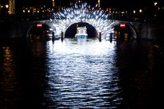 A boat passes through a light filled tunnel in Amsterdam, Nether royalty free stock photography
