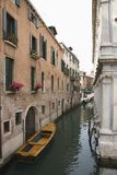 Canal with boat and buildings in Venice. Stock Photos