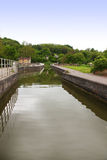 Canal boat entering lock with trees, reflection, c. Ottage and bridge in united kingdom near Bath Stock Image