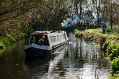 A canal boat passing anglers on the river. royalty free stock image