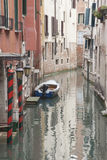 Canal with Boat and Red Brick Facade, Venice Stock Image