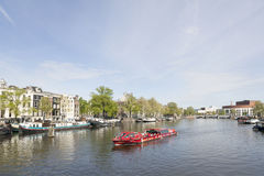 Canal boat on river amstel in amsterdam Stock Images
