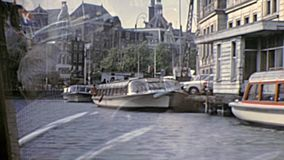 Canal Boat Tour Amsterdam Cruise. AMSTERDAM, HOLLAND - CIRCA 1976: sea view of Amsterdam Boat Tour boats on the river. Historical archival Canal Boat Tour Cruise stock video footage