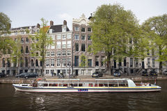Canal boat with tourists in Golden bend of herengracht on sunny Stock Photos