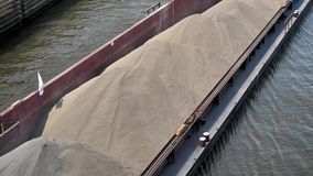 Canal boat transports sand over waterway stock video