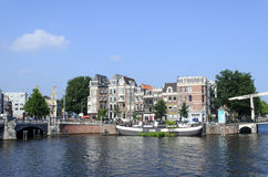Canal with boats in Amsterdam. A view of boats on the canal in harbor on 26 July 2014 in Amsterdam, The Netherlands Stock Image