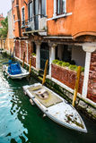 Canal with boats and colorful facades of old medieval houses in Venice Stock Photos