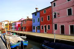 Canal with boats and colorful houses in Burano in Venice in Italy Stock Image