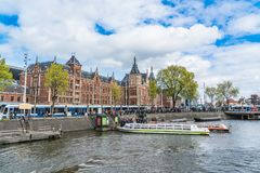Canal boats in front of the Central station in Amsterdam. The famous Central station with in front lots of tourists getting into canal boats to view the city Stock Image