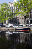 Canal with boats and homes amsterdam holland Stock Photos