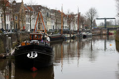 Canal boats and houses. Scenic view of canal boats moored on quayside of town with row of houses Stock Photos