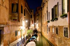Canal with boats and a small bridge in Venice at night, Italy. Venice postcard. Royalty Free Stock Photos