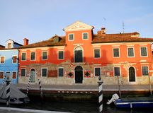 Canal with boats, a stately home light red in Burano Venice area Italy Royalty Free Stock Images