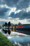 Canal boats under moody sky. A row of canal boats on a British canal with a cloudy moody sky reflected in the water royalty free stock photography