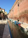 Canal with boats in Venice. Small canal with boats in Venice, Italy, on a sunny day. Narrow side canal with boats docked alongside a high brick wall Stock Photos