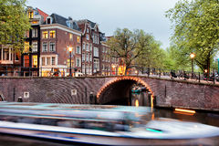 Canal Bridge and Boat Tour in Amsterdam at Evening. Canal bridge and passenger boat tour at evening in the city of Amsterdam, Netherlands, North Holland province Royalty Free Stock Images