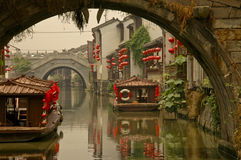 Canal Bridge In Suzhou, Shanghai. A view under a bridge to another ancient bridge with canal boats decked out with red lanterns in Suzhou, near Shanghai, China Stock Photos