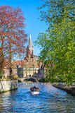Canal and bridge view, boat with tourists, church tower in Brugge, Belguim Royalty Free Stock Photo