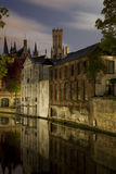 Canal in Bruges. Medieval buildings along a canal in Bruges, Belgium, at night, with the famous Belfry in the middle of the image Royalty Free Stock Image