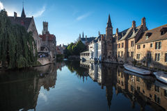 Canal in Bruges. Images showing a canal in Bruges. Medieval Buildings reflect in the canal water in a calm afternoon Stock Photo