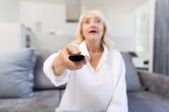 Canal cambiante de la mujer mayor con teledirigido en casa Fotos de archivo libres de regalías