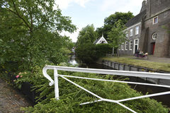 A canal and church in the Dutch town of Broek in Waterland. Greenery and a church line a canal in the village of Broek in Waterland in the Netherlands Stock Photography