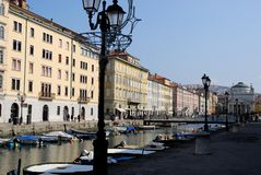 Canal com barcos, postes de luz e construções sob o céu azul em Trieste em Friuli Venezia Giulia (Itália) foto de stock