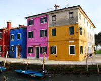 Canal com os barcos, duas cores e outras cores brilhantes na área Itália de Burano Veneza imagens de stock
