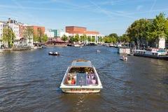 Canal con la reconstrucción de gente en un barco de cruceros en Amsterdam Fotos de archivo libres de regalías