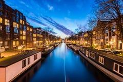 Canal con los barcos de casa en Amsterdam Países Bajos Imagen de archivo