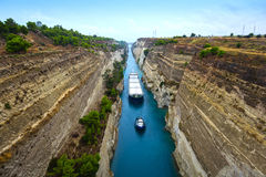 Canal of Corinth. Tug leads cargo vessel in the narrow Canal of Corinth, Greece Stock Image